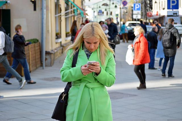 blondýna, zelený kabátek, mobil
